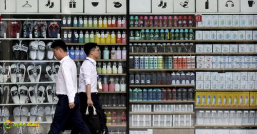 Chinese men walk by a global chain store selling household items in Beijing, Monday, July 31, 2017. (AP Photo/Andy Wong)